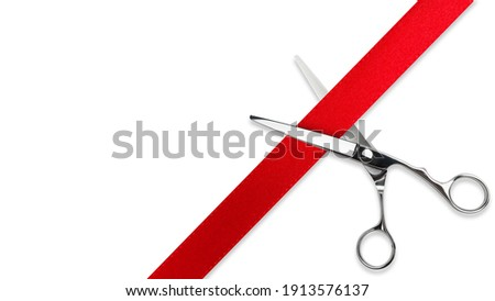 Scissors Grand opening. Top view of scissors cutting red silk ribbon against white isolated background with copy space. Silver stainless metal scissors or shears. Royalty-Free Stock Photo #1913576137