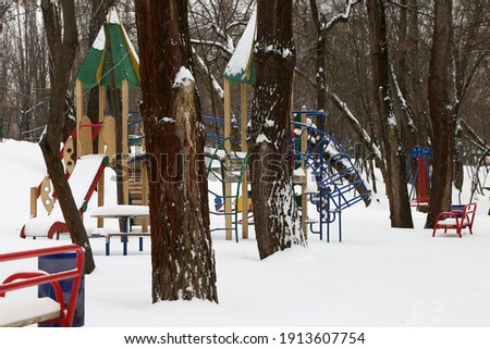 playground in winter in the park in the snow