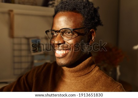 Close up picture of cheerful positive young dark skinned guy in stylish eyeglasses and sweater looking with radiant smile, having optimistic facial expression, thinking about future, making plans