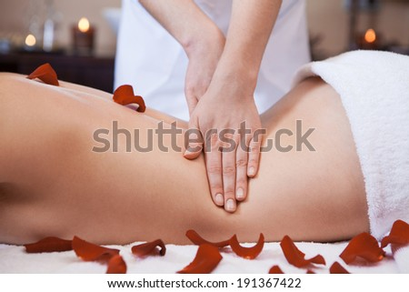 Massage. A photo of a beautiful young woman getting a massage on a massage table scattered with roses.