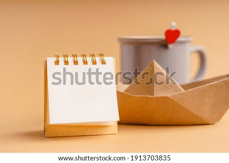 An empty blank notebook for notes in the foreground against the background of a mug with a heart and a craft paper boat