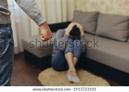 The alcoholic husband beats his wife with his fist. Zhenzhina covers herself with her hands. Violence in family Royalty-Free Stock Photo #1913723101