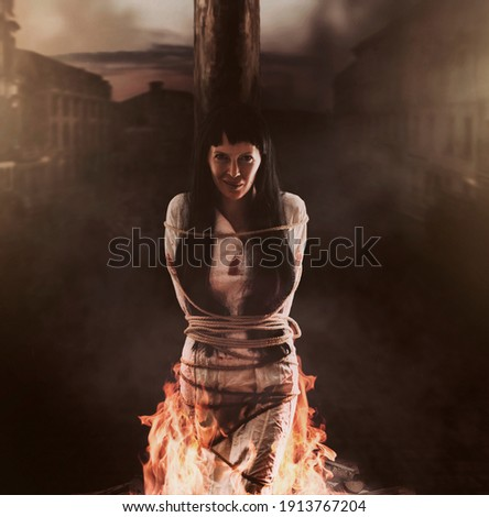 Medieval witch is tied to a wooden post and burns at the stake and smile Royalty-Free Stock Photo #1913767204