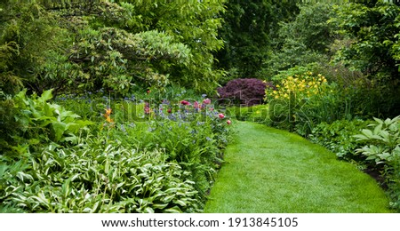 Lush green botanical garden - blooming spring flowers and lawn path. Royalty-Free Stock Photo #1913845105