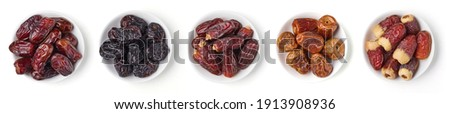 Set of various dates in bowl, isolated on white background; top view Royalty-Free Stock Photo #1913908936