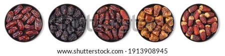 Set of various dates on black plate isolated on white background; top view Royalty-Free Stock Photo #1913908945