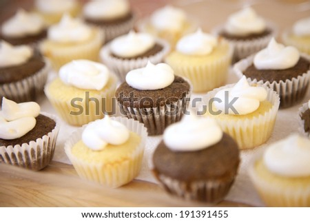 Home baked chocolate and vanilla mini cupcakes with butter cream frosting  #191391455