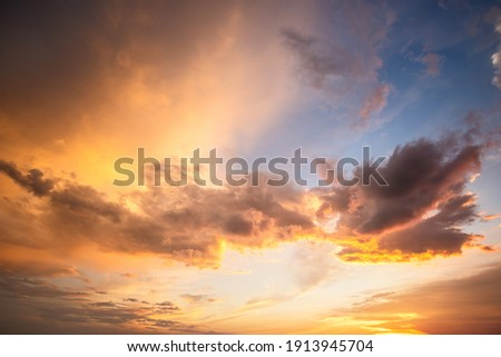 Dramatic sunset landscape with puffy clouds lit by orange setting sun and blue sky. Royalty-Free Stock Photo #1913945704