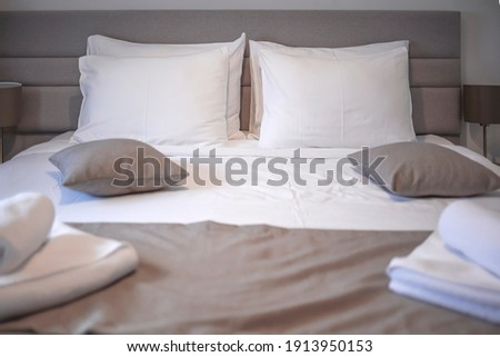 Modern bedroom with white bed. Bed maid-up with clean white pillows and bed sheets in beauty bedroom. Close-up. Interior background. Modern bedroom with  bed and set of white color tone pillows