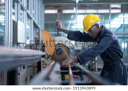 Engineer wearing safety uniform control operating lathe grinding machine working in industry factory. African american engineer cutting steel pipe at factory workshop, black people, worker concept