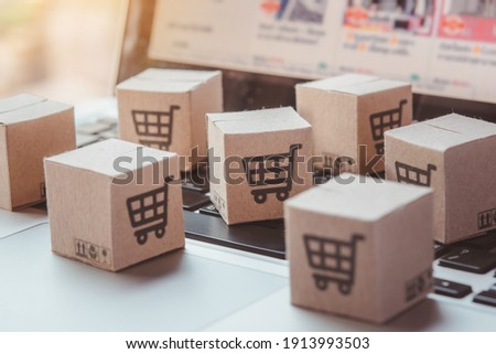 Shopping online. Cardboard box with a shopping cart logo on laptop keyboard. Shopping service on The online web. offers home delivery Royalty-Free Stock Photo #1913993503