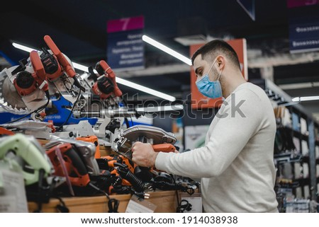 Young man in mask choosing circular saw in hardware store Royalty-Free Stock Photo #1914038938