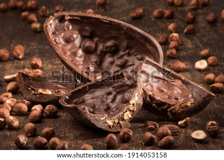 Stuffed chocolate easter egg on a wood table with hazelnuts. Royalty-Free Stock Photo #1914053158