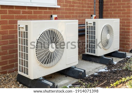 Two air source heat pumps installed on the exterior of a modern house Royalty-Free Stock Photo #1914071398