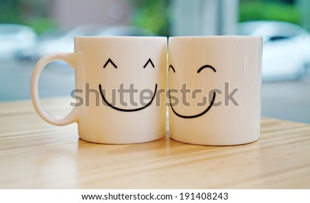 Two happy cups with black polka dot tablecloth. Concept about love and relationship #191408243