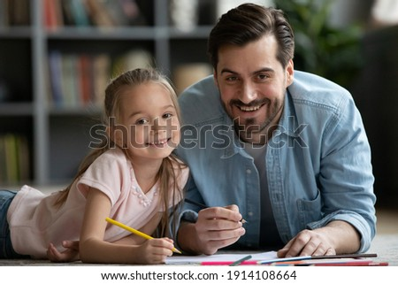 Head shot portrait of young handsome father lying on floor with adorable little preschool child daughter, enjoying drawing pictures in album at home, happy different generations family hobby activity.