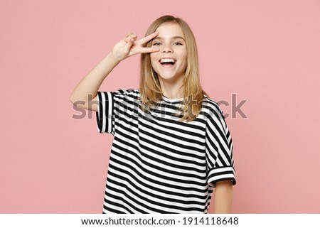Little blonde smiling kid girl 12-13 years old wearing striped oversized t-shirt cover eye with victory v-sign gesture isolated on pastel pink background children studio. Childhood lifestyle concept Royalty-Free Stock Photo #1914118648