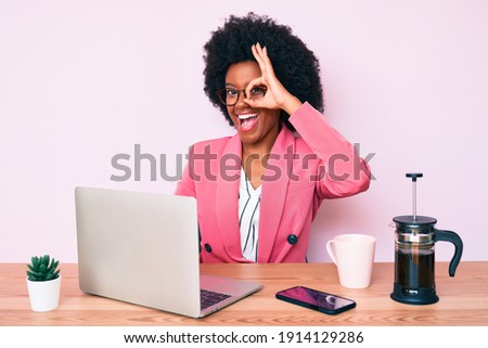 Young african american woman working at desk using computer laptop smiling happy doing ok sign with hand on eye looking through fingers