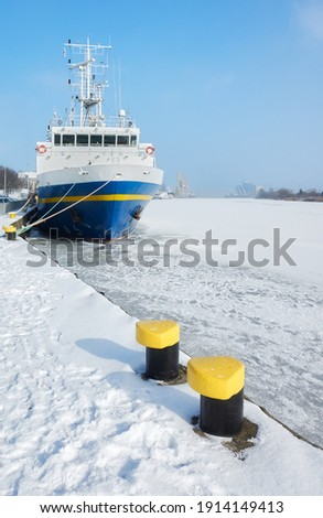 Mooring bollards on a pier by frozen Odra River in Szczecin, Poland. Royalty-Free Stock Photo #1914149413