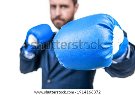 Businessman stand in fighting position wearing blue boxing gloves selective focus, punching. Royalty-Free Stock Photo #1914166372