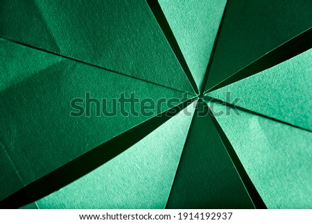 Abstract radial green background of folded textured paper. Close-up image. Concepts: origami, color, lines and geometry.