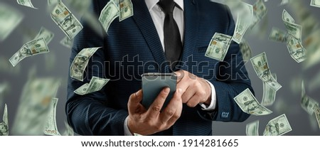 Online sports betting. A man in a suit is holding a smartphone and dollars are falling from the sky. Creative background, gambling Royalty-Free Stock Photo #1914281665