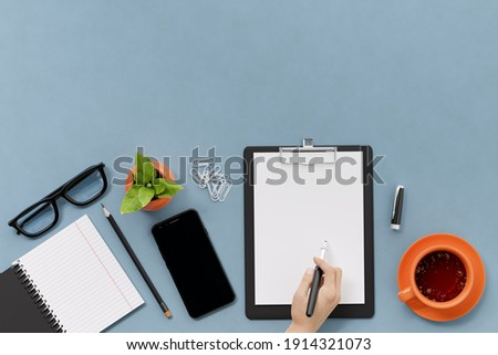 Office, business utensils on a blue table, telephone, a cup of tea, pencils, a notebook, glasses, a plant in a pot. Hand signing the document. 3d illustration. Render.