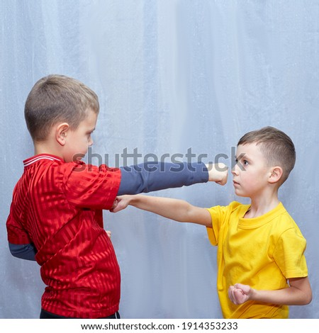 Athletes in red and yellow T-shirts perform punches to meet each other Royalty-Free Stock Photo #1914353233