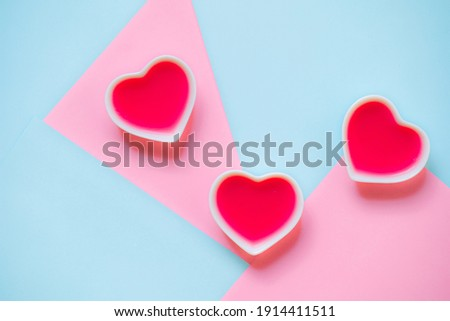 Gelatin three red hearts in the white porcelain bowls on the pastel blue and pink geometrical smooth background. Concept of Valentines Day, romance, affair and love. Trendy beautiful food photography. Royalty-Free Stock Photo #1914411511