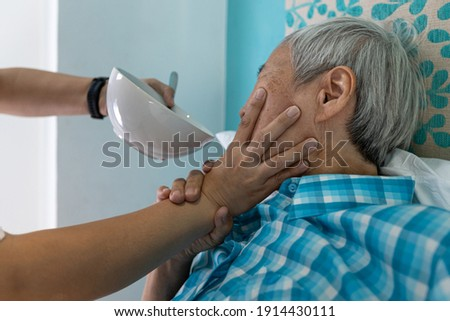 Force-feeding,Asian senior woman refuses,does not want to eat food,caregiver scolding,forcing the elderly to eat,old people with no appetite,stop physical abuse,violence,aggression,coercion concept Royalty-Free Stock Photo #1914430111