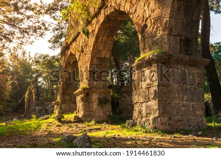 Ruins of the aqueduct of the ancient ancient city of Phaselis illuminated by the bright sun in sunny weather in Turkey, Antalya, Kemer. Turkey national nature landmarks. Gates to ancient city Royalty-Free Stock Photo #1914461830