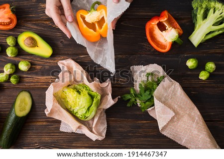 Top view of female hands wrapping vegetables into beeswax wraps. Zero waste kitchen with reused packaging materials. Royalty-Free Stock Photo #1914467347