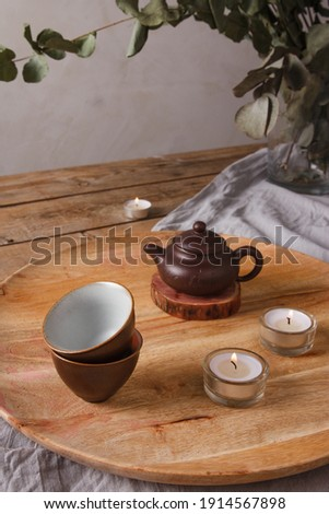 Traditional Asian Tea Set - ceramic teapot and teacups for tea ceremony on a wooden table. Vintage style. With space for text. China, tea, tableware, tradition, health, tea ceremony, Asia. Royalty-Free Stock Photo #1914567898