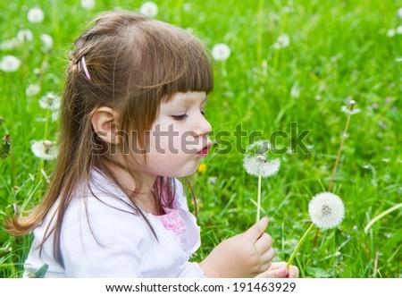 Lovely little blond little girl blowing a dandelion #191463929