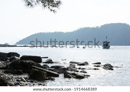 Boat in the sea against the background of misty mountains with rocks on the beach in the foreground at cloudy weather in Turkey, Phaselis Royalty-Free Stock Photo #1914668389