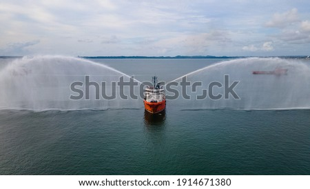 An offshore support vessel testing her fire fighting system to ensure readiness of the system whenever required to be used in an emergency. Royalty-Free Stock Photo #1914671380