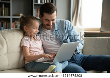 Smiling little girl with father using laptop together at home, sitting on cozy couch in living room, looking at screen, watching video or cartoons, shopping online, chatting, enjoying leisure time