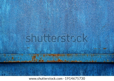 The blue metal fence is covered with ice water. Ice glistens in the sun on blue metal. Reflections of the sun on the surface of a blue icy surface. .Blue paint metal plate texture and background. Royalty-Free Stock Photo #1914675730