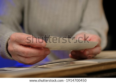 Elderly woman looks through an family album with old photos at table at home. Old granny memories past times and remembering his life.