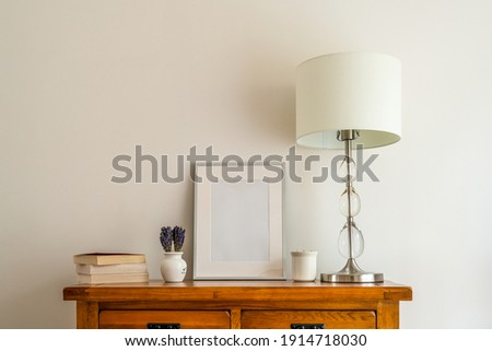 close up of room interior  oak side board with  mock up silver picture frame, books, lamp with shade and china pot  and lavender floral arrangement in small vase