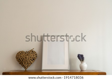 oak side board close up with  mock up silver picture frame,rattan heart and china vase with Lavender floral arrangement Life Style close up