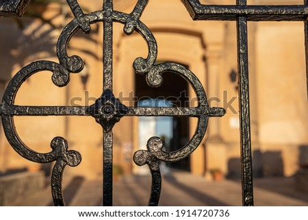 Close-up of the black metal grille at the main entrance of the Municipal Cemetery of Porreres, island of Mallorca, Spain. In the background, the entrance to the cemetery out of focus Royalty-Free Stock Photo #1914720736