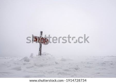 """A homemade snow-covered warning sign with the inscription """"STOP"""" set on a mountainside ."""