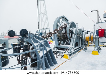 The mooring deck of a cargo ship with anchor winches, an anchor chain on winches, bollards and haws with mooring ropes, frozen and covered in snow. Snow on the mooring deck of a cargo ship. Royalty-Free Stock Photo #1914736600
