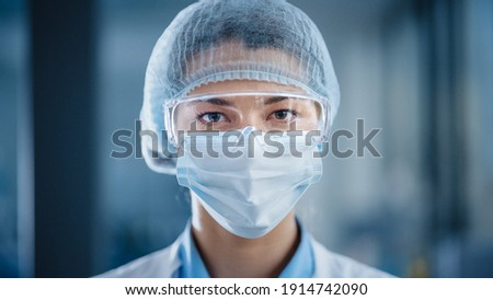 Close Up Portrait of a Beautiful Female Doctor or Surgeon Wearing a Protective Face Mask, Goggles and Disposable Surgical Cap. Laboratory Scientist Calmly Looking at Camera. Covid-19 Pandemic Concept. Royalty-Free Stock Photo #1914742090