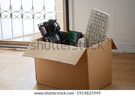 Old hard disk dive and motherboards and used keyboard with mouse old computer hardware accessories in paper boxes, Obsolete equipment is electronic waste Reuse and Recycle concept. Royalty-Free Stock Photo #1914825949