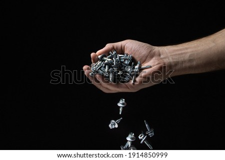Roofing screws on a black background. Metal building material. Self-tapping screws pouring from a man's hand Royalty-Free Stock Photo #1914850999