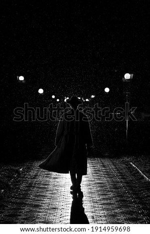 dark silhouette of a man in a coat and hat in the rain on a night street in the city in the style of Noir Royalty-Free Stock Photo #1914959698