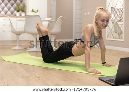 young attractive girl is engaged in fitness at home and looks at the laptop. quarantine fitness concept. high quality