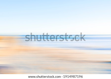 Coastal beachside blur in soft tones of blue and brown. Royalty-Free Stock Photo #1914987196